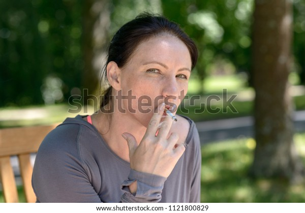 Portrait of mature woman smoking cigarette in park on sunny day