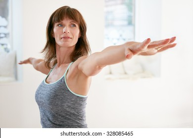 Portrait of mature woman stretching her arms and looking away at gym. Beautiful woman performing yoga in warrior pose, Virabhadrasana.