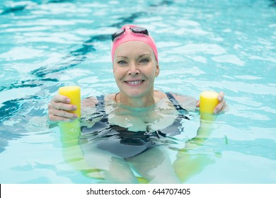 Portrait of mature woman swimming with pool noodle