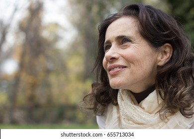 Portrait of mature woman with a vision look in her eyes at park during fall season. Intellectual young looking lady with positive thinking look. Autumn fashion sales concept