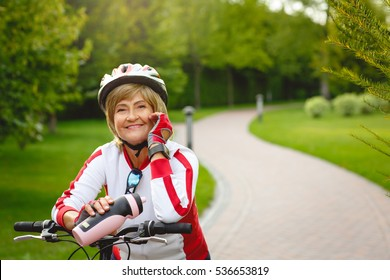 Portrait of mature woman, wearing protective helmet, on her bike in the beautiful park. Healthy and active retirement concept