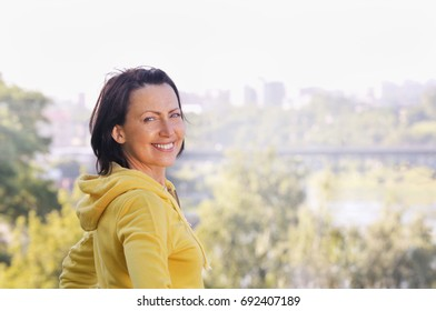 Portrait of mature woman wearing in sports clothes in the park. Attractive looking mature woman keeping fit and healthy