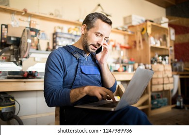 Portrait of mature worker using laptop and speaking by smartphone  in workshop interior, copy space