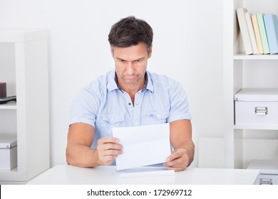 Portrait Of A Mature Worried Man Looking At Document