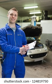 Portrait of mechanic in coverall writing on clipboard at garage