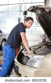Portrait of a mechanic man leaning on car in garage