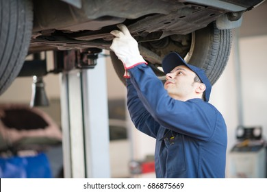 Portrait of a mechanic repairing a lifted car
