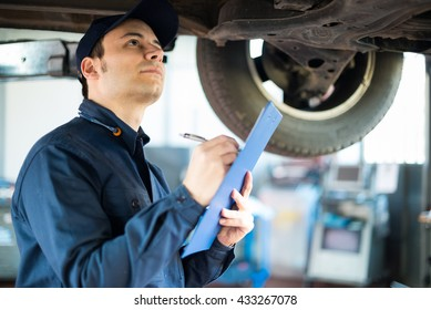 Portrait of a mechanic taking notes while inspecting a car