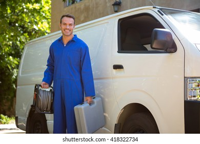 Portrait of mechanic with a tool box and cable standing near a car