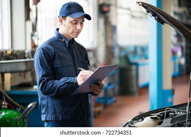 Portrait of a mechanic writing on a clipboard