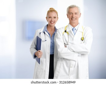 Portrait of medical team standing at hospital. Senior professor with arms crossed and female doctor holding clipboard in her hand while looking at camera and smiling.
