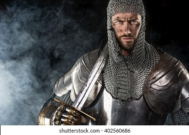 Portrait of Medieval Dirty Face Warrior with chain mail armour and red cross on sword. Cloud smoke on Dark Background