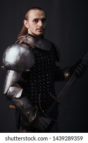 Portrait of a medieval knight with a two-handed sword. Warrior in the studio on a dark background.