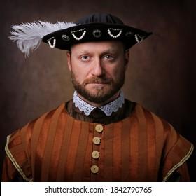 Portrait of medieval man in vintage clothing on dark background.