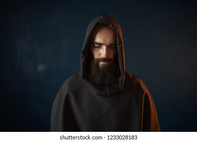 Portrait of medieval monk in black robe with hood