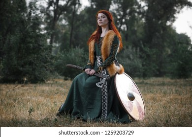 Portrait of a medieval viking girl in a long dress with an ax in the forest