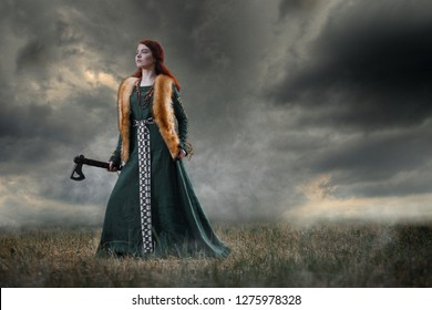 Portrait of medieval viking girl in long dress with axe. Cosplay photo