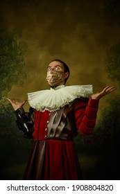 Portrait of medieval young man in vintage clothing, golden face mask looks wondered, astonished on dark background. Royal person protected from covid. Concept of comparison of eras, modern, fashion.
