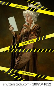 Portrait of medieval young woman in brown vintage clothing on dark background with limiting tape with word Lockdown. Concept of comparison of eras, modern, coronavirus. Blocked social life.