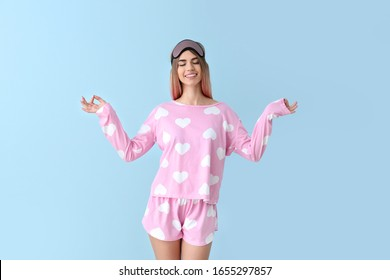 Portrait of meditating woman in pajamas and with sleep mask on color background