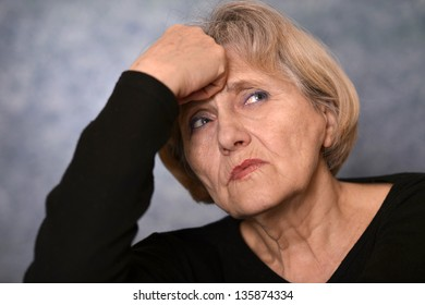 portrait of melancholy older woman in a black sweater on a gray background