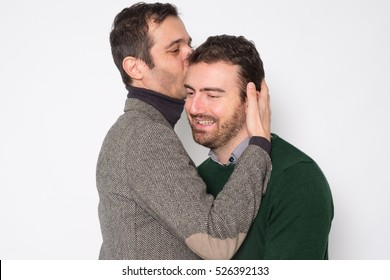 Portrait of a men gay couple in studio kissing each other