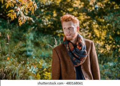 Portrait of a men. A red-haired man on leafs background.