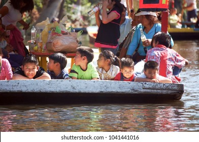 Portrait of Mexican children in Xochimilco, January 2009, Xochimilco, Mexico City, Mexico: A group of Mexican children lay on the edge of a traditional gondola in the canal of Xochimilco market.