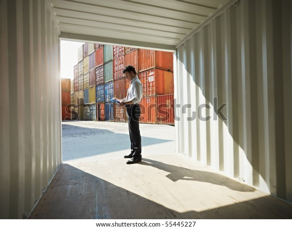 portrait of mid adult businessman standing near cargo container and writing on clipboard. Horizontal shape, side view, copy space