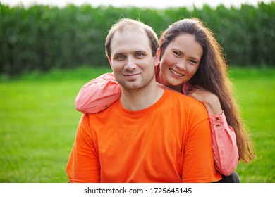 Portrait of mid adult couple looking at camera and smiling outdoors. Happy young embracing her husband in park. Love, relationships, family
