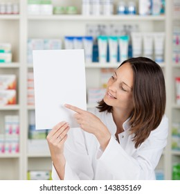 Portrait of mid adult female pharmacist pointing on blank paper at pharmacy