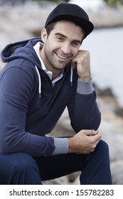 Portrait of mid adult man in cap and hooded top