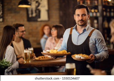 Portrait of mid adult waiter serving food to guests in a tavern and looking at camera.