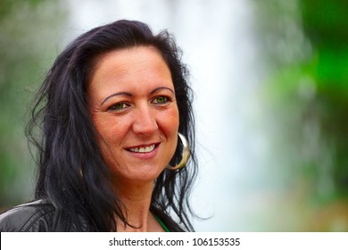 Portrait of a mid adult woman in background a fountain, outdoor in a small city D i l l i n g e n, S a a r l a n d  / Germany