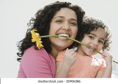 Portrait of a mid adult woman with her daughter holding a flower in their teeth