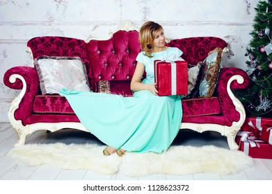 Portrait of mid adult woman sitting on sofa with Christmas gift