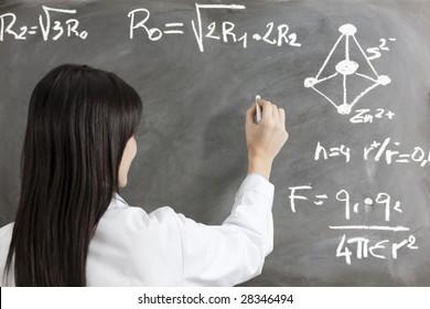 portrait of mid adult woman writing chemical formula on blackboard