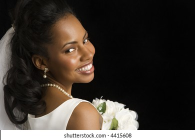 Portrait of a mid-adult African-American bride on black background.