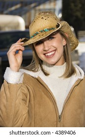 Portrait of a mid-adult Caucasian female holding brim of her cowboy hat.