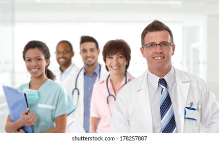 Portrait of mid-adult caucasian male doctor with medical team in background.