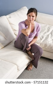 Portrait of mid-adult woman sitting on couch at home
