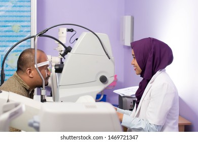 portrait of middle age asian man having eye examinating check with digital optometry tools with Hijab Female ophthamologists on clinic room -image