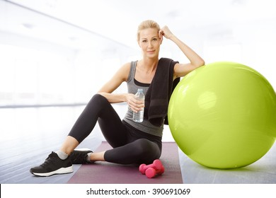 Portrait of middle age beautiful woman holding in her hand a bottle of water while sitting at yoga mat and relaxing after fitness workout.