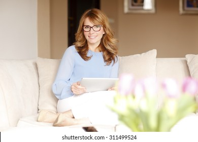 Portrait of middle age business woman sitting at sofa and holding digital tablet in her hands. Mature woman working at home.