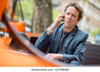Portrait of a middle age businessman sitting on the terrace of a coffee shop and speaking on the phone.