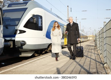 Portrait of a middle age businesswoman and a senior businessman walking on railway platform after business trip.