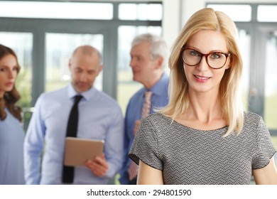 Portrait of middle age businesswoman standing in foreground while business people standing behind her. Business persons using digital tablet and consulting. Teamwork at office.