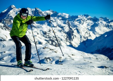 Portrait of middle age man in green jacket skiing in French Alps on sunny winter day, Tignes.