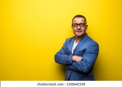 Portrait of middle age man in suit and eyesglasses isolated on yellow background