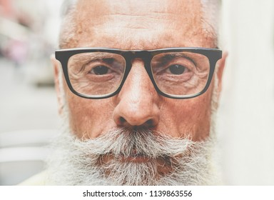 Portrait of middle age trendy man with serious expression - Close up of bearded senior guy - Fashion and elderly lifestyle concept - Focus on glasses